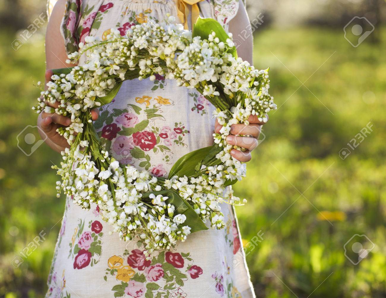 Little girl holding wreath from lily of the valley in her hands - 50767280