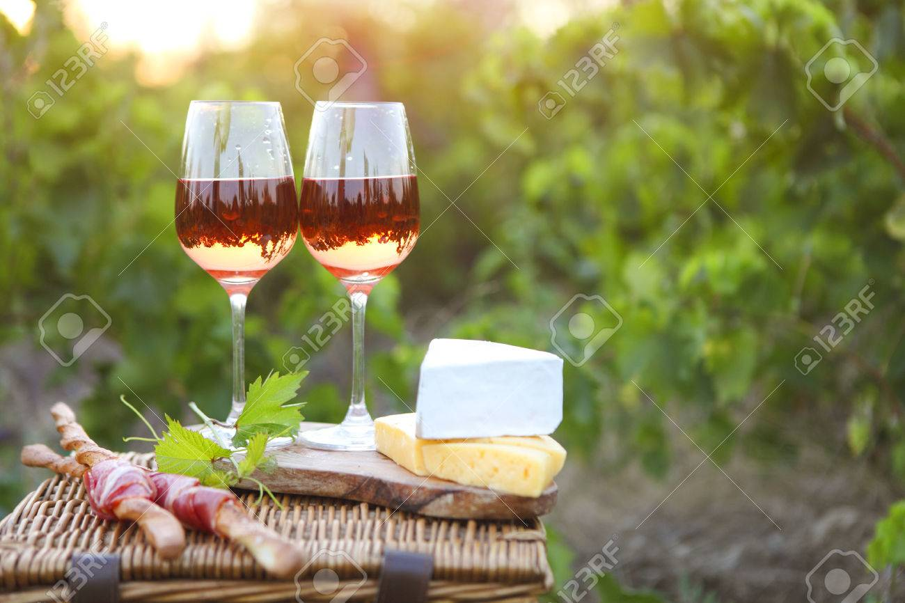Two glasses of rose wine with bread, meat, grape and cheese on the vineyard background - 51372199