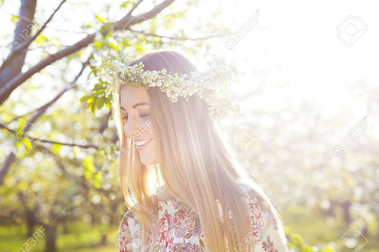 Beautiful romantic woman with long blond hair in a wreath of lily of the valley in the spring garden - 51247350