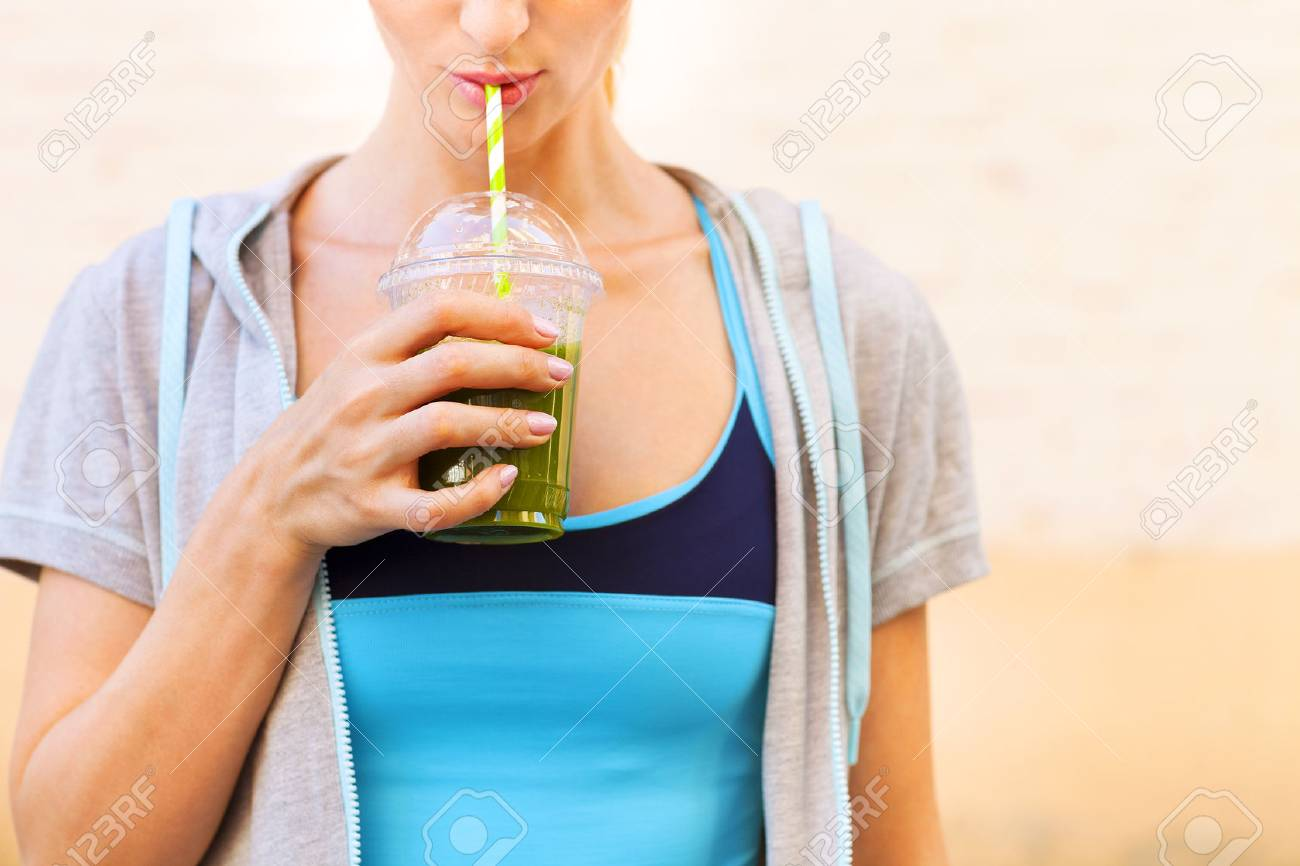 Woman drinking vegetable smoothie after fitness running workout on summer day. Fitness and healthy lifestyle concept - 51247467