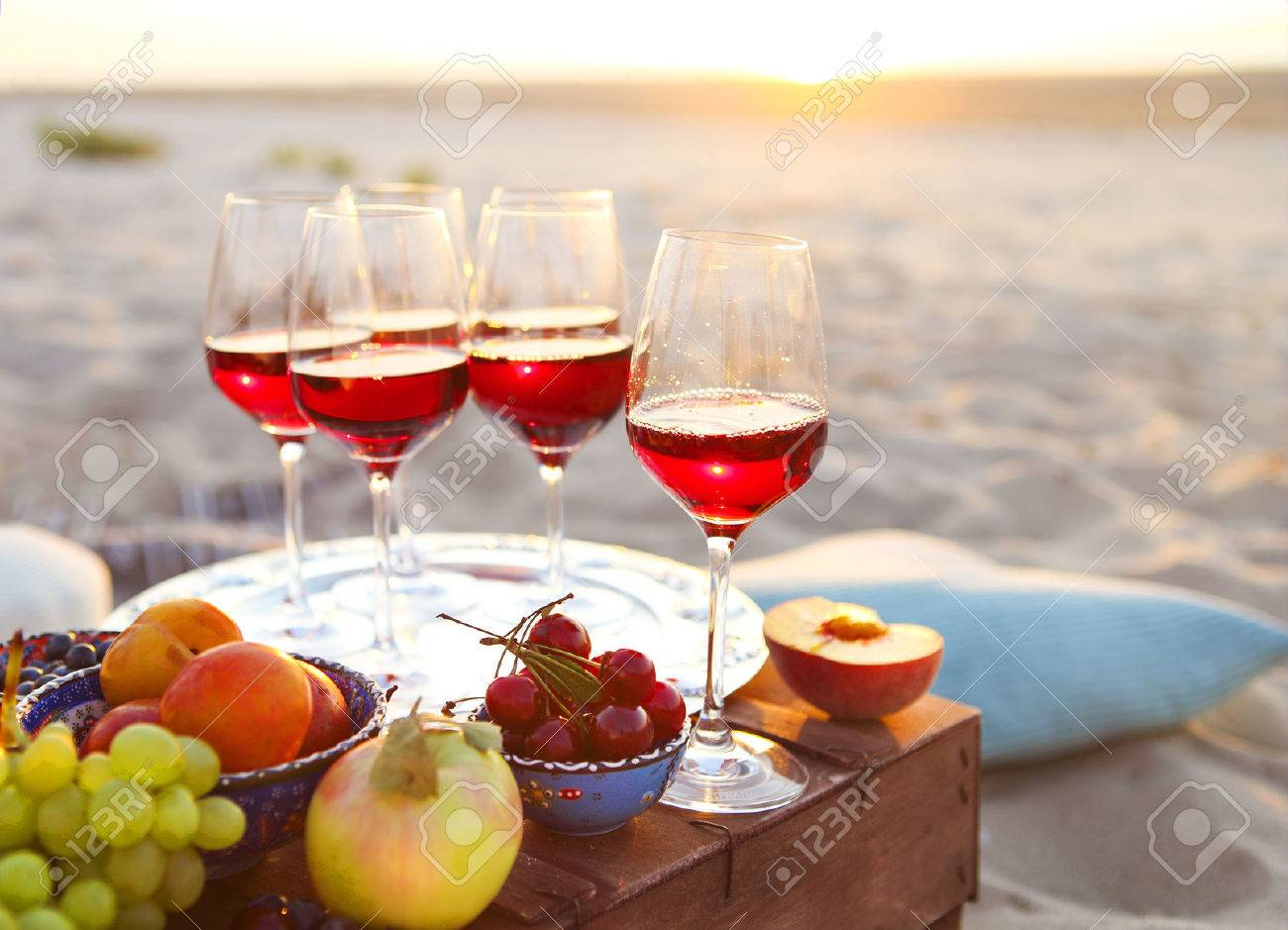 Glasses of the red wine on the sunset beach picnic - 52124916