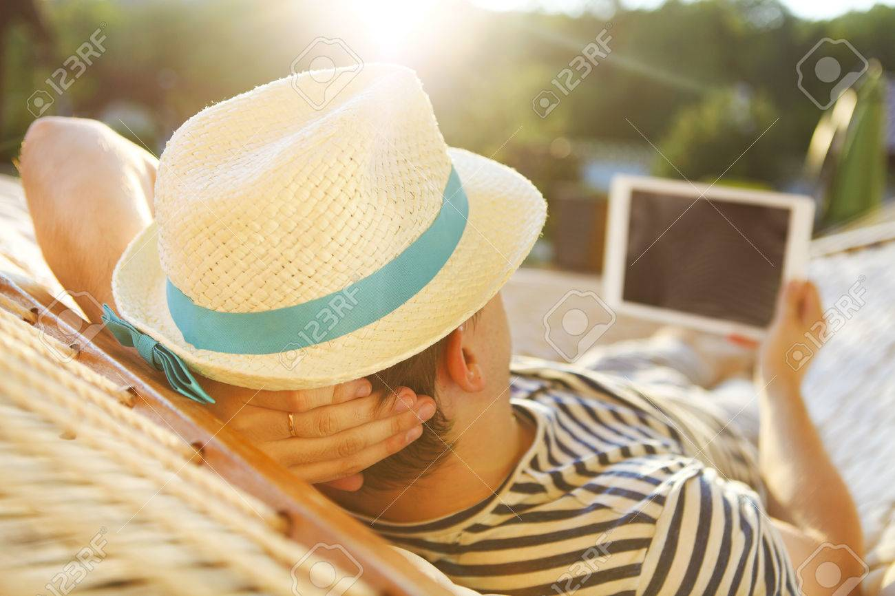 Lazy time. Man in hat in a hammock with tablet computer on a summer day - 51871950