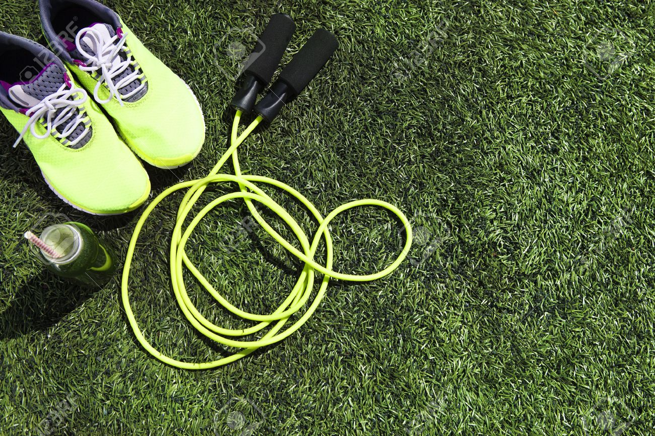 Running shoes, jump rope and drink bottle with green juice on grass background - 52141721