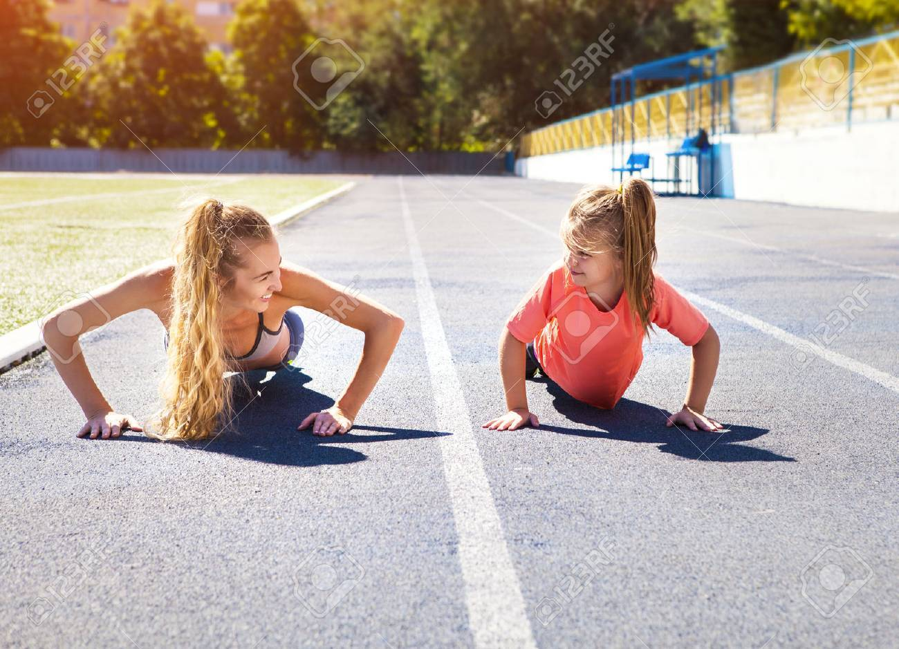 Mother and little daughter are doing exercise in the stadium. Family doing fitness at the stadium. Healthy family concept - 52314765