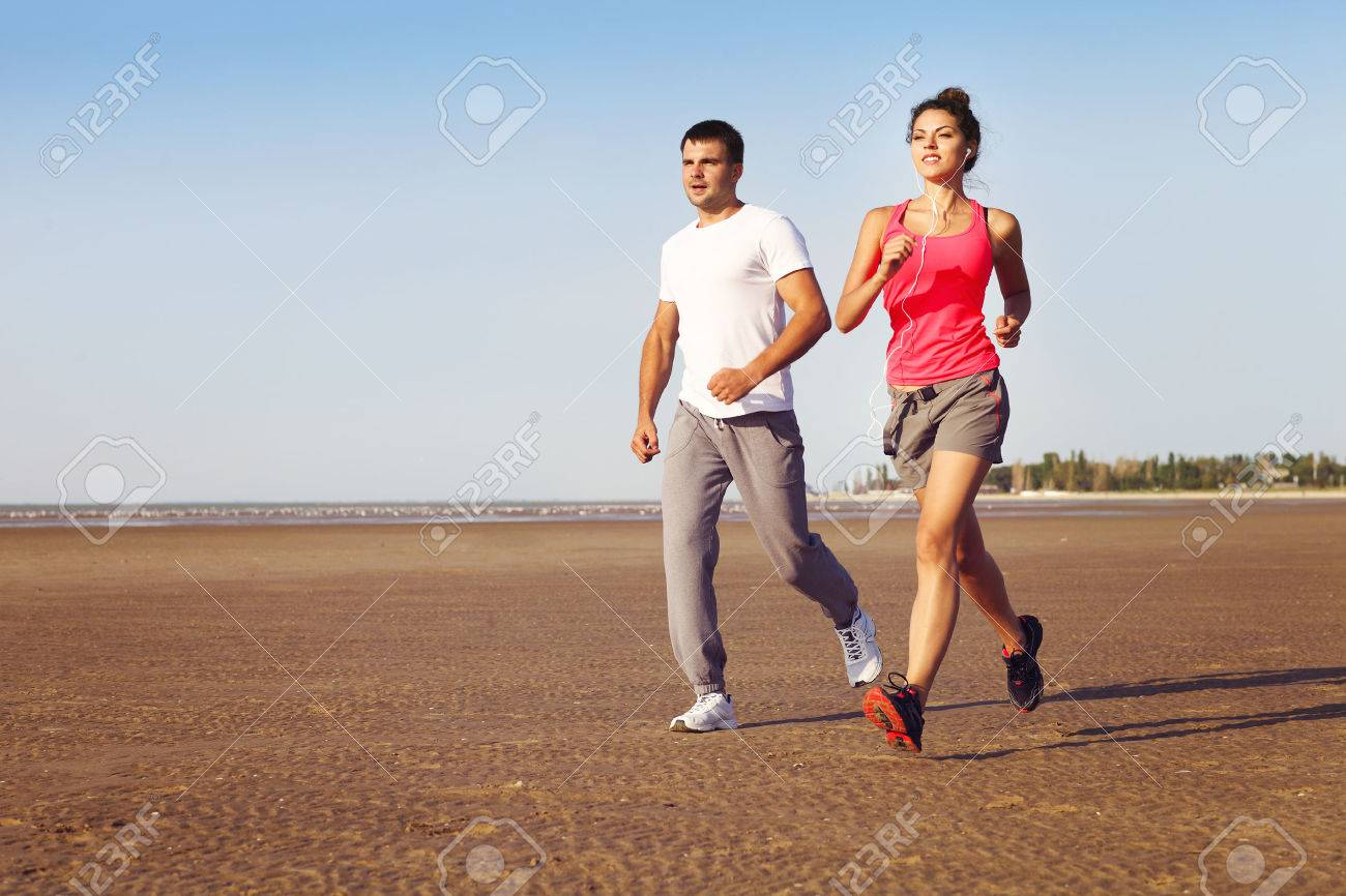 Portrait of couple jogging outside, runners training outdoors working out in nature against blue sky - 52315486