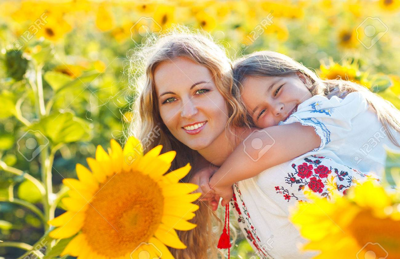 Happy mother and her little daughter in the sunflower field. Summer fun - 52315511
