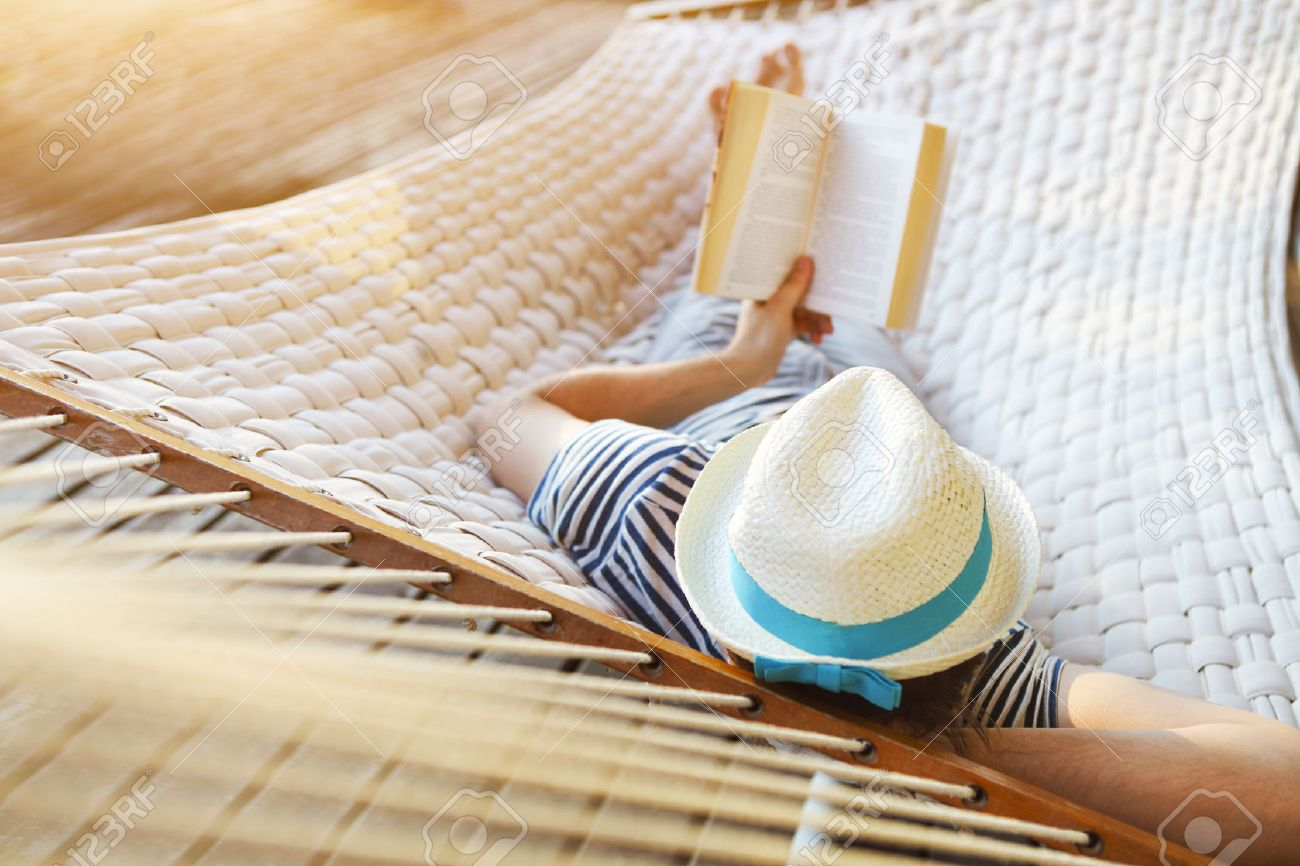 Lazy time. Man in hat in a hammock with book on a summer day - 52546932