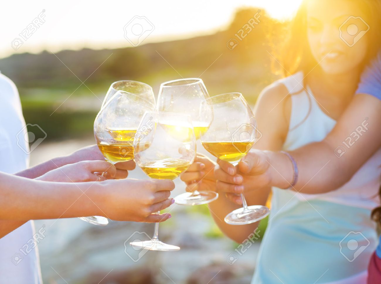 Celebration. People holding glasses of white wine making a toast. Sunset summer party - 52674474