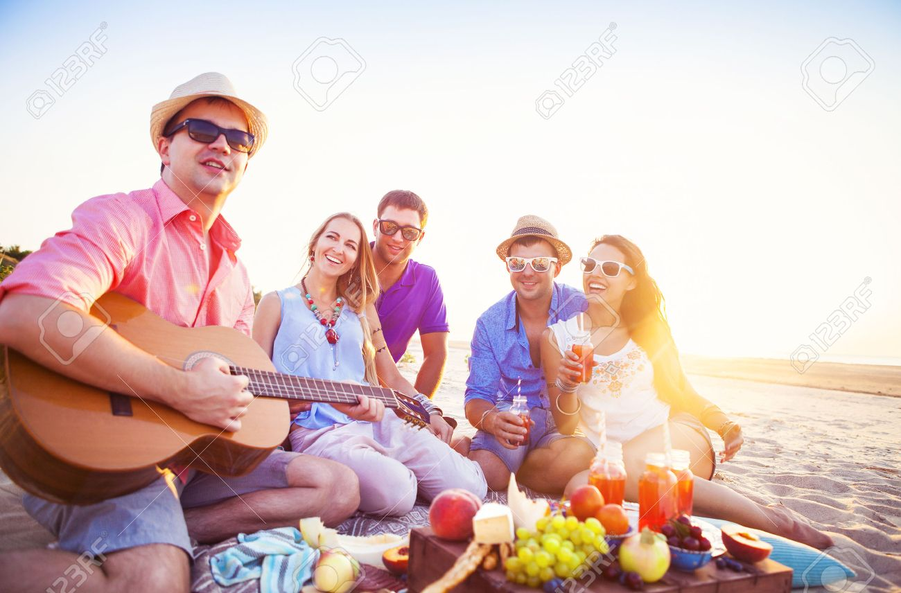 Friends sitting on the sand at the beach in circle. One man is playing guitar - 52963671