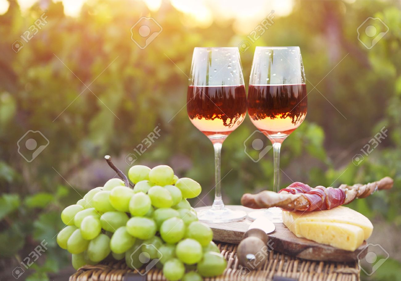 Two glasses of rose wine with bread, meat, grape and cheese on the vineyard background - 54379875