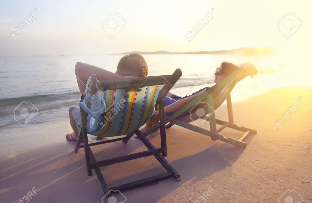 Happy couple sitting at sun chairs on the beach of Koh Samet at sunset, Thailand - 53914868