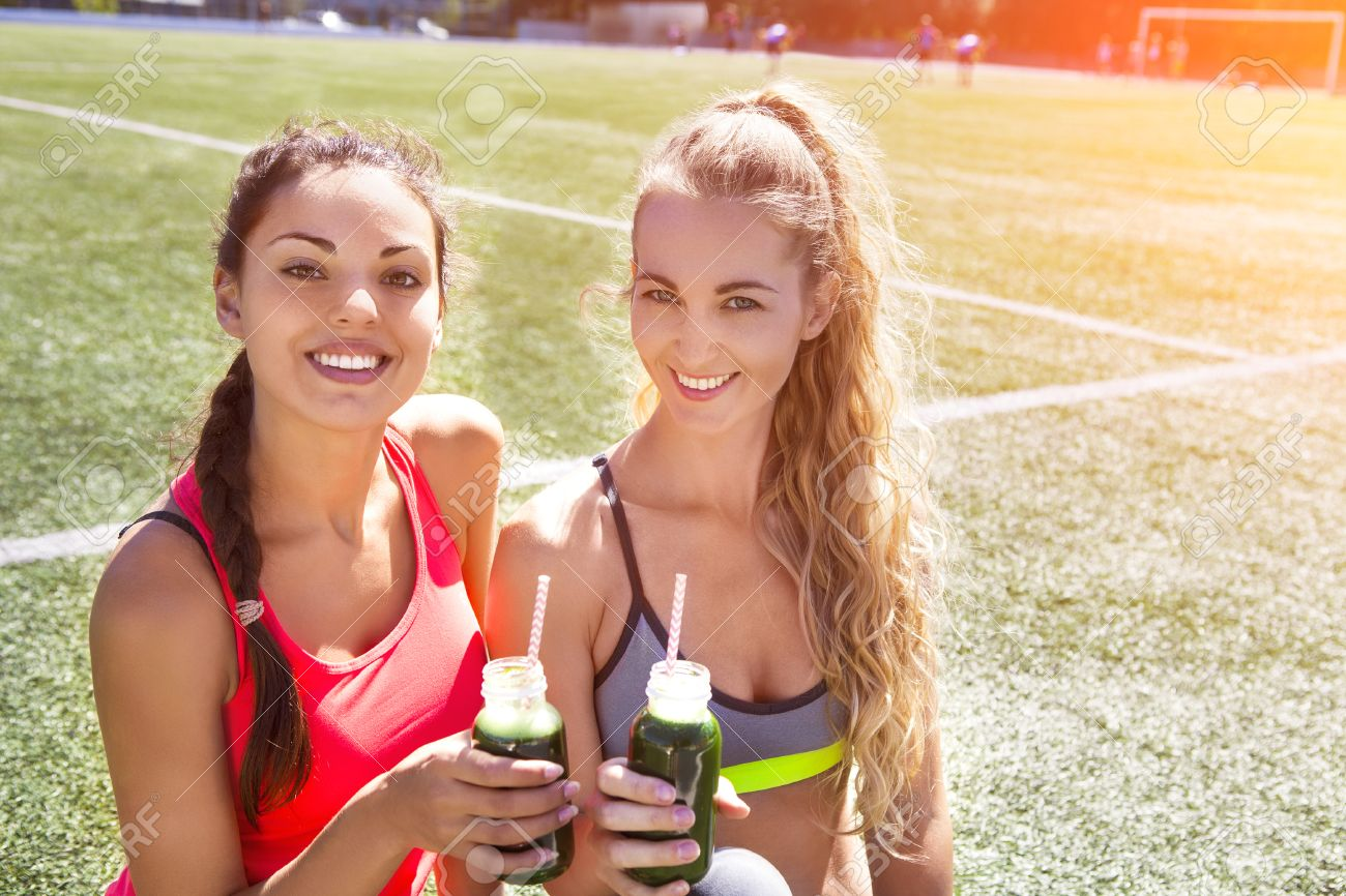 Two happy women drinking vegetable smoothie after fitness running workout on stadium. Fitness and healthy lifestyle concept - 53914872