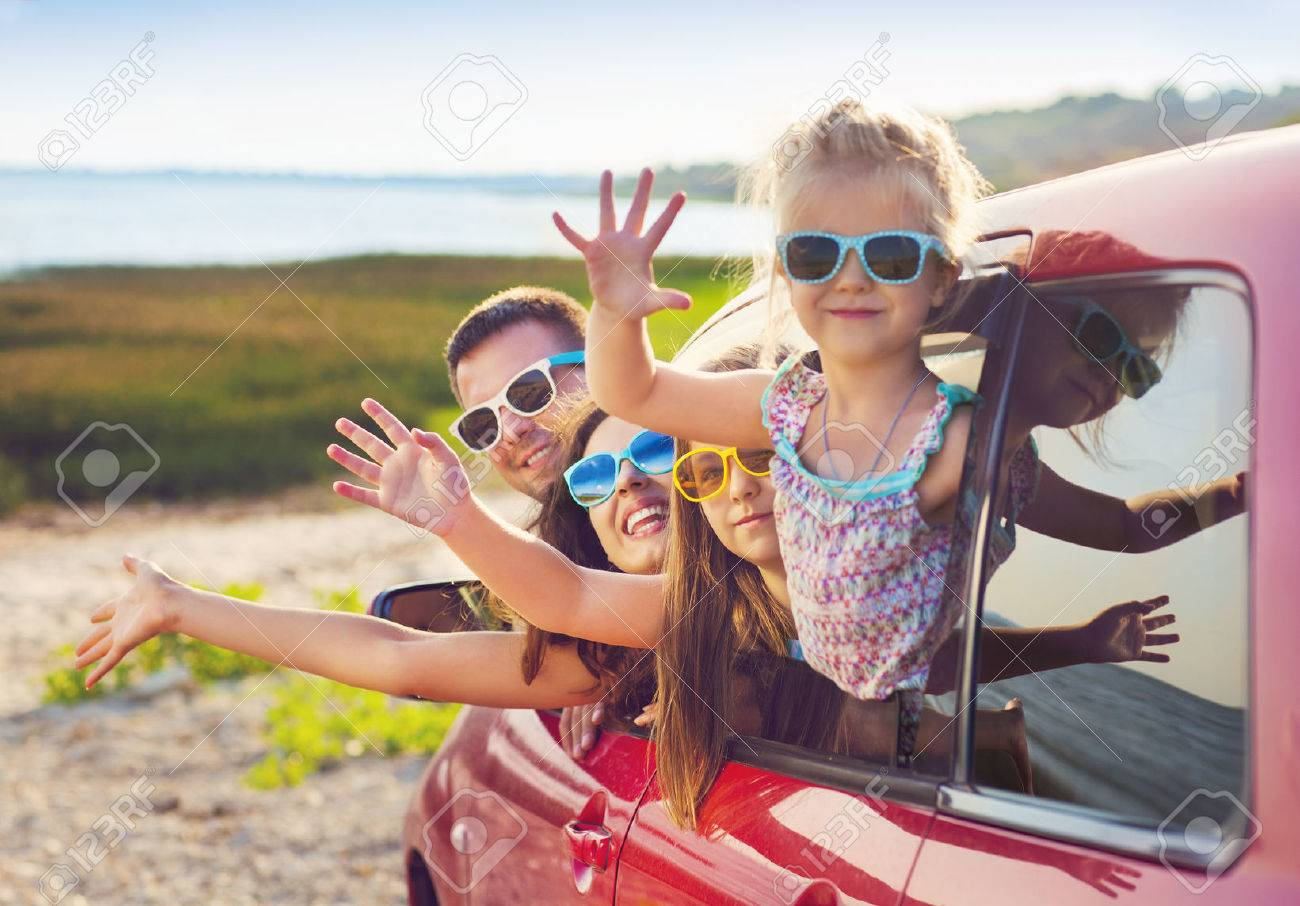 Portrait of a smiling family with two children at beach in the car. Holiday and travel concept - 54379909