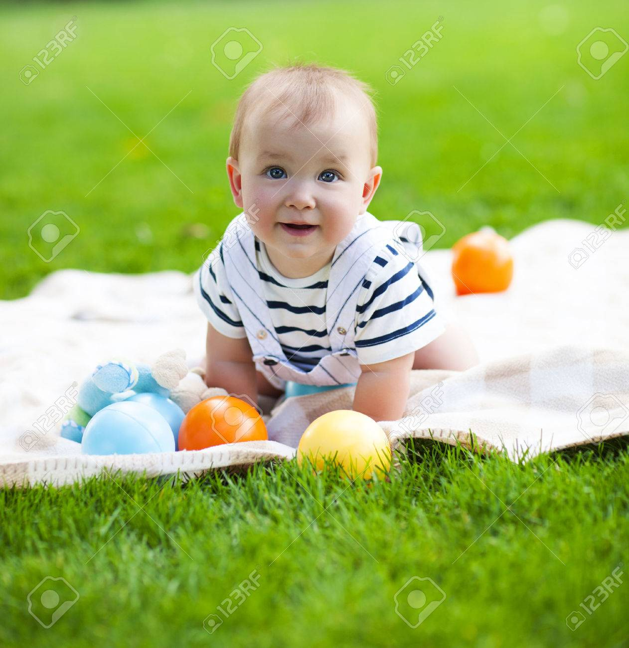 Close up portrait of the smiling baby boy playing outdoors - 54379904