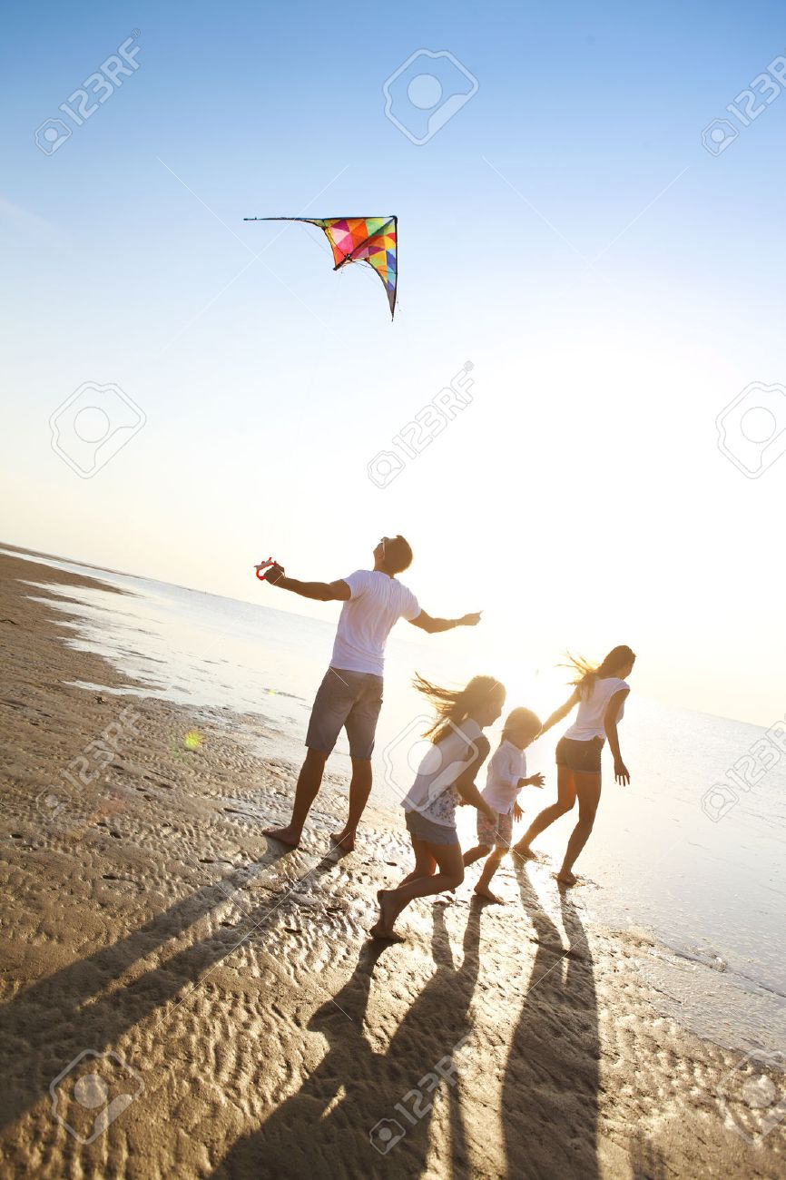Happy young family with two kids with flying a kite on the beach - 55843852