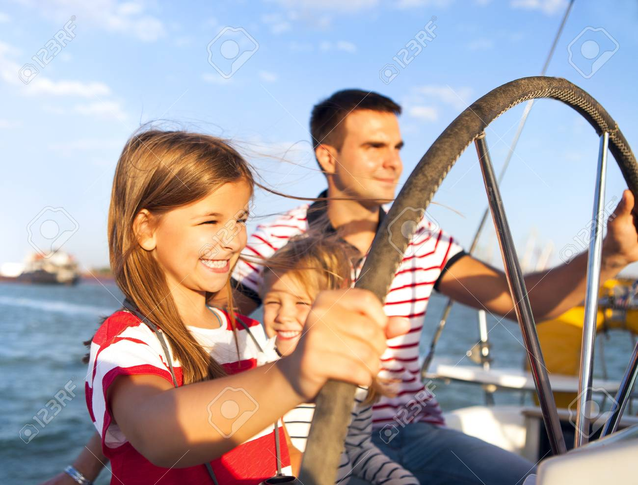 Young father with adorable daughters resting on a big boat - 57290512
