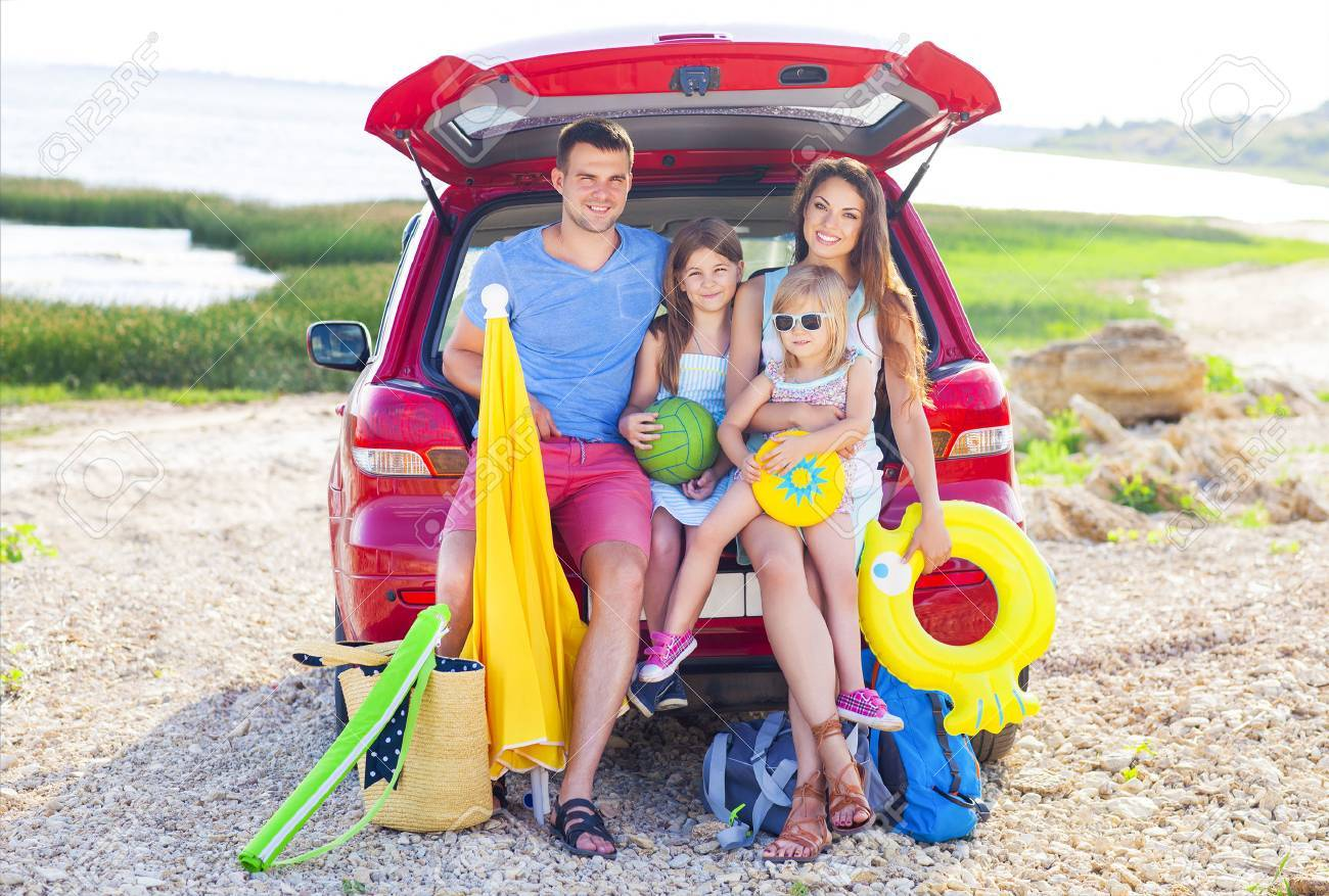 Portrait of a smiling family with two children at beach by car. Holiday and travel concept - 57290516