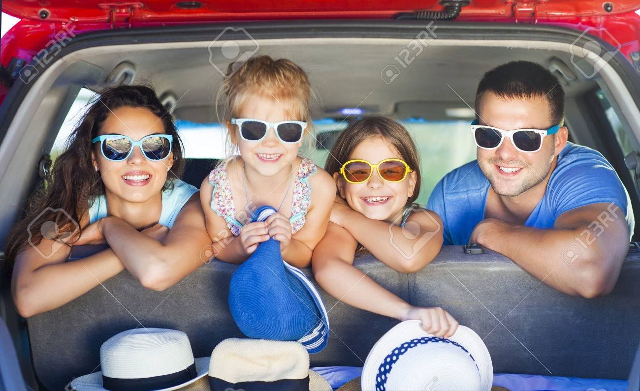 Portrait of a smiling family with two children at beach in the car. Holiday and travel concept - 57292319