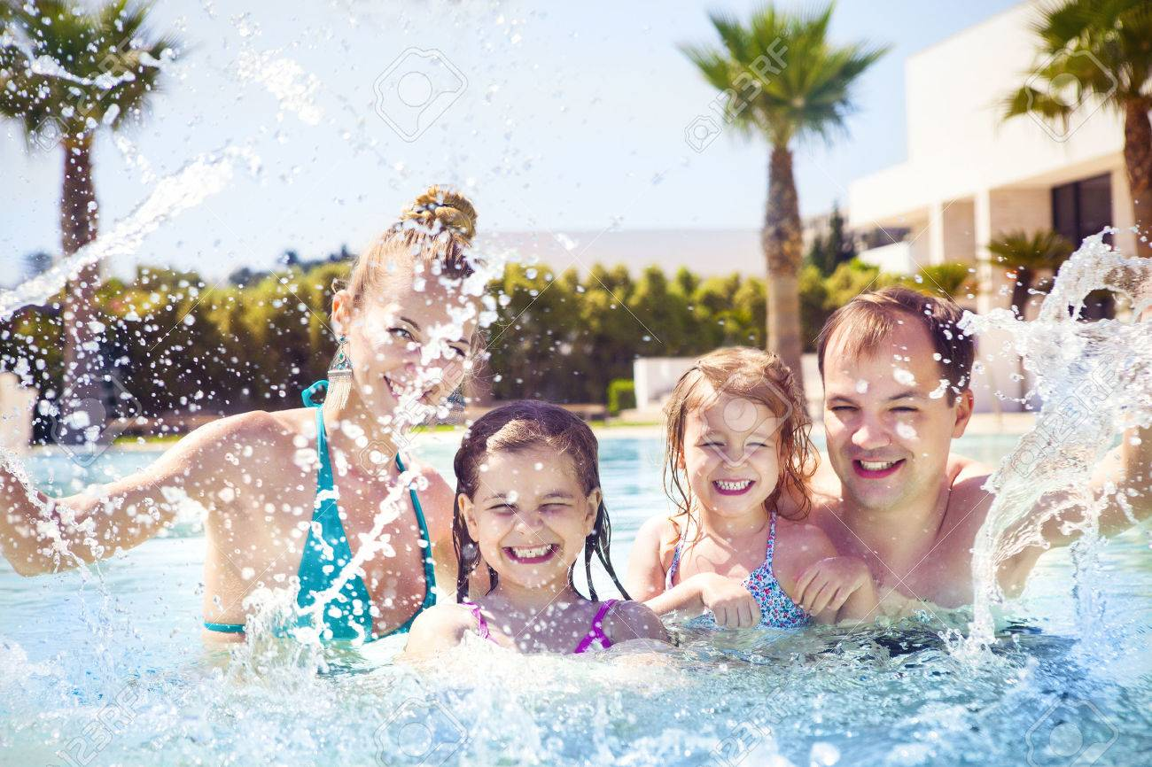 Happy family with two kids having fun in the swimming pool. Summer vacation concept - 57292326