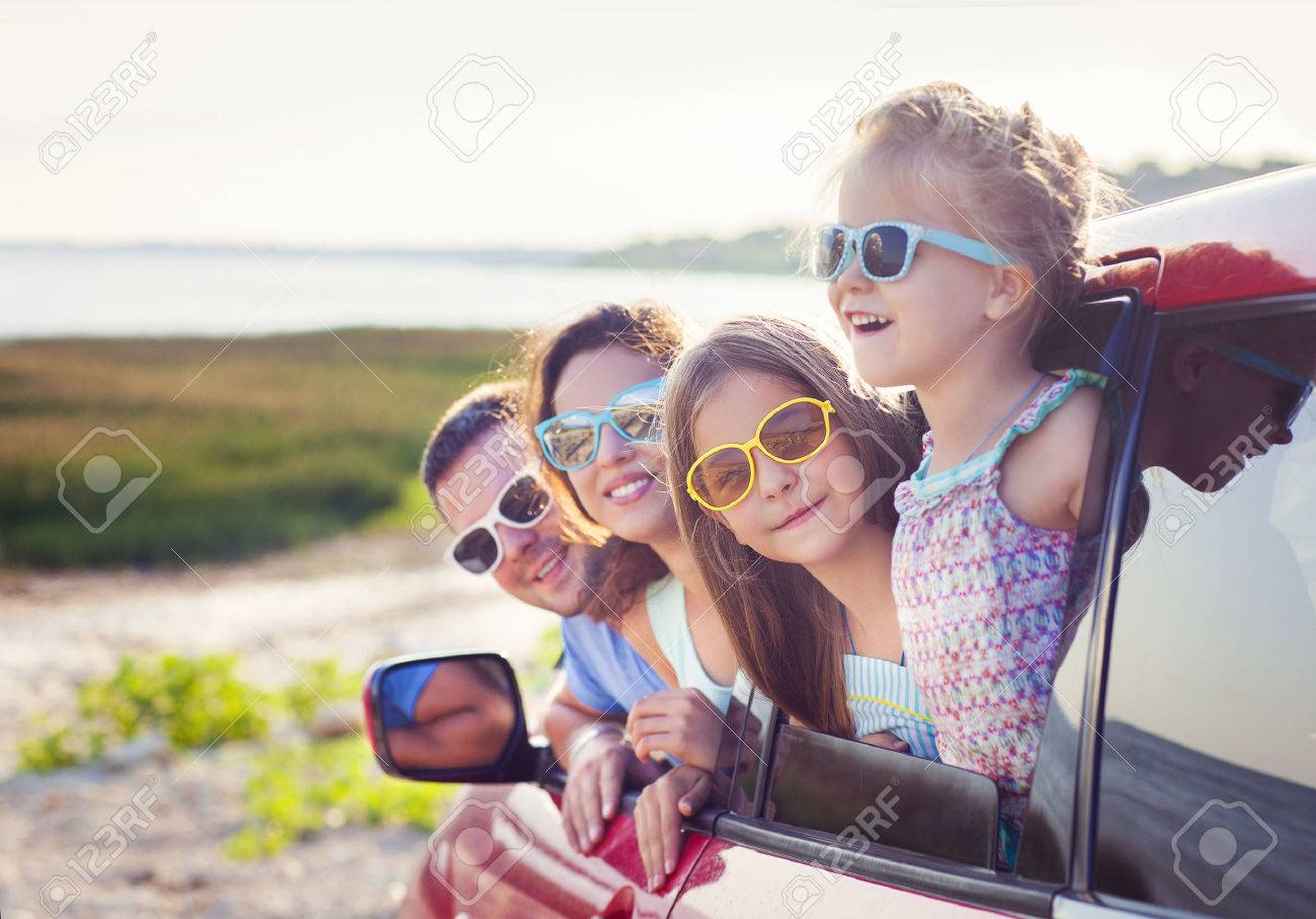 Portrait of a smiling family with two children at beach in the car. Holiday and travel concept - 57292338