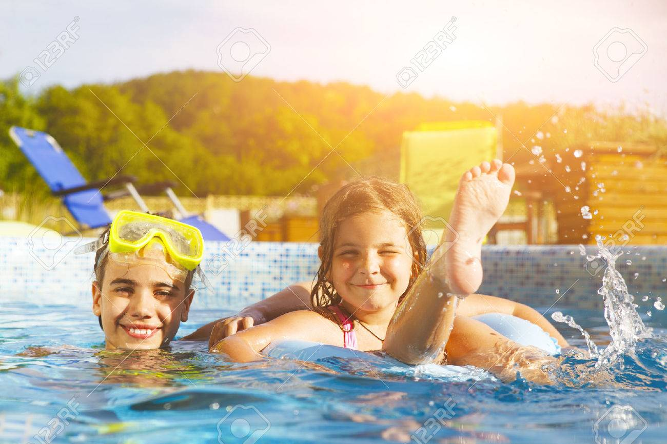 Children playing in pool. Two little girls having fun in the pool. Summer holidays and vacation concept - 57292342