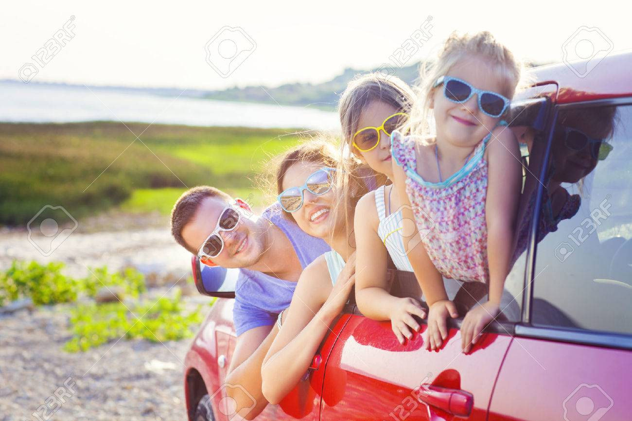 Portrait of a smiling family with two children at beach in the car. Holiday and travel concept - 59660435