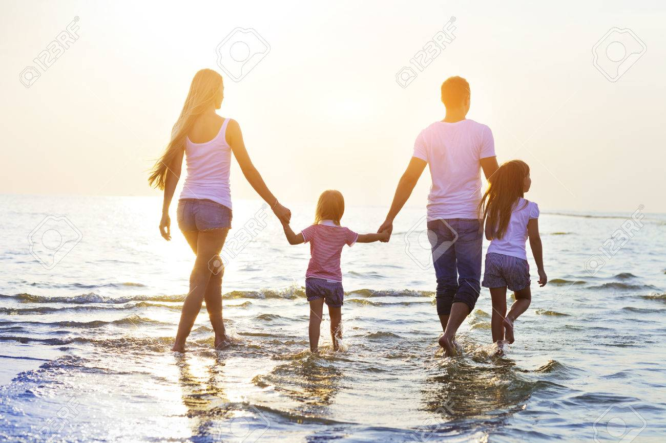 Happy young family having fun running on beach at sunset. Toned photo. - 60415761
