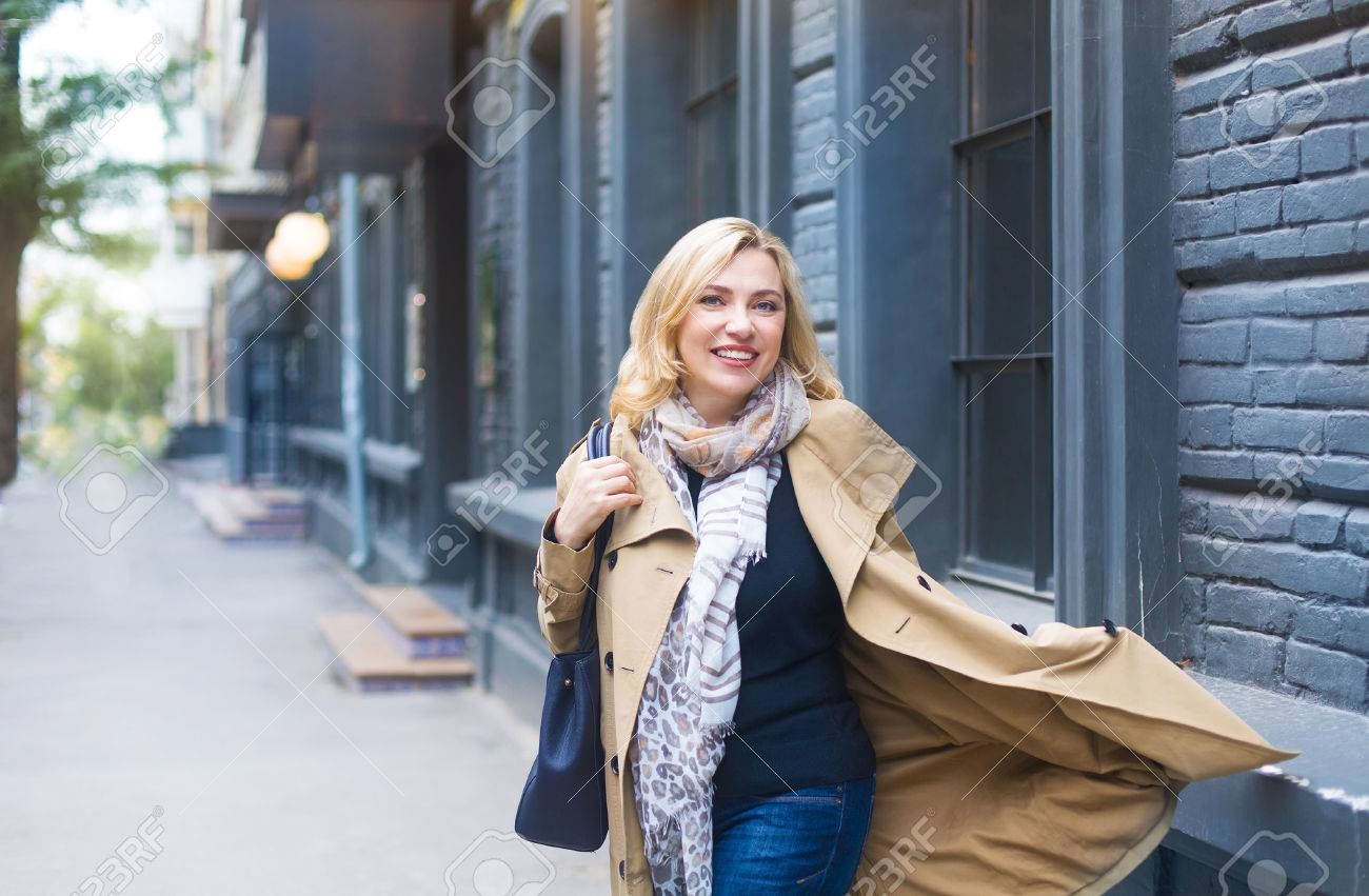 Middle age woman goes through the city and smiles. Happiness concept. - 70536455