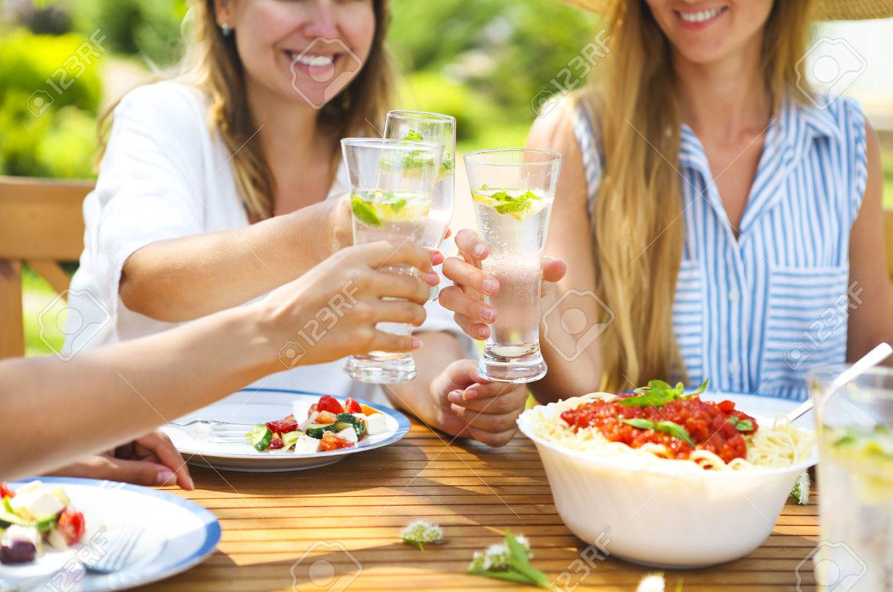 Happy female friends with glasses of lemonade at dining table in lawn. Close up - 78820000
