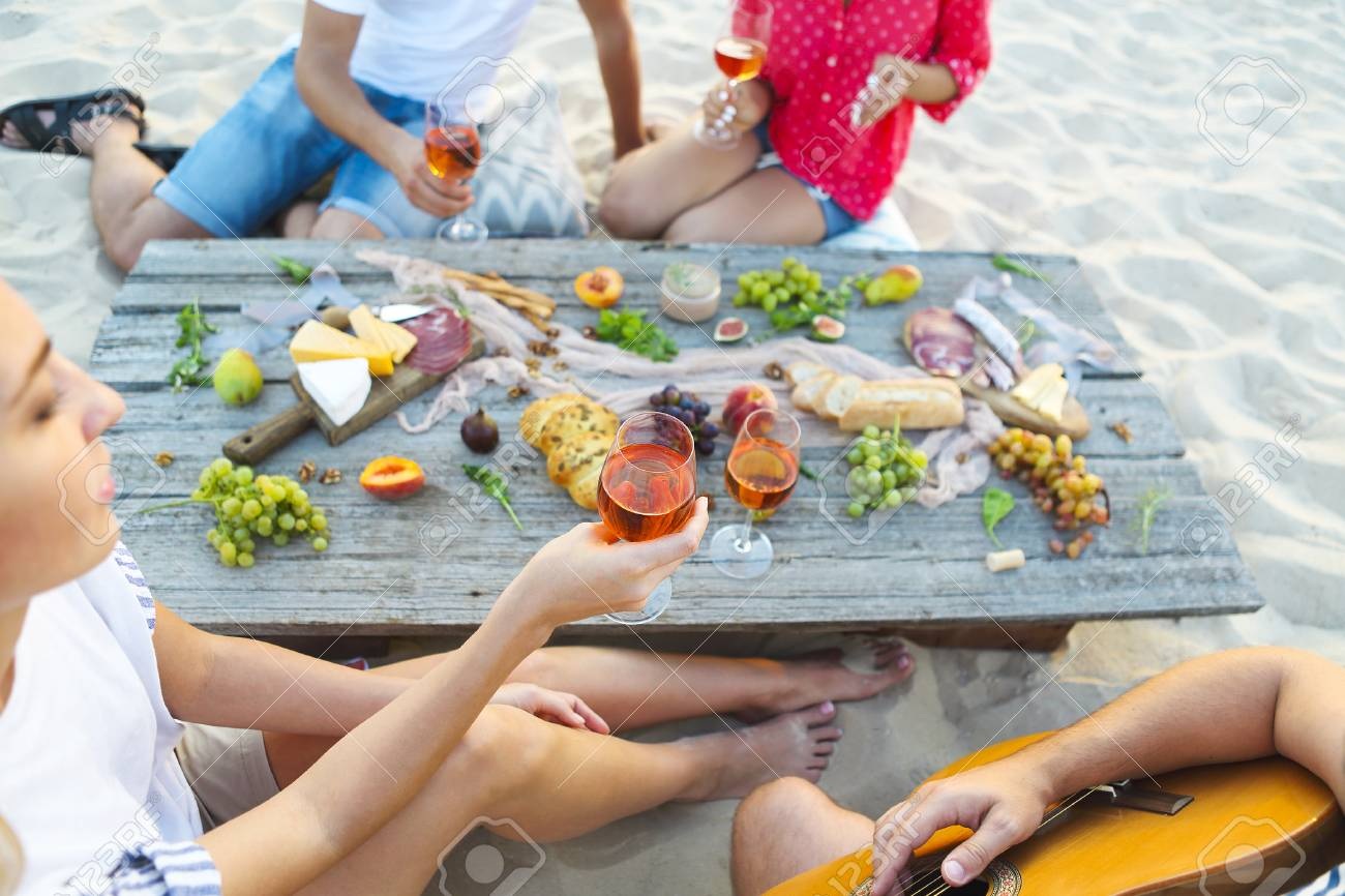 Young friends drinking rose wine on summer beach picnic. Summer vacation and party concept - 81603574