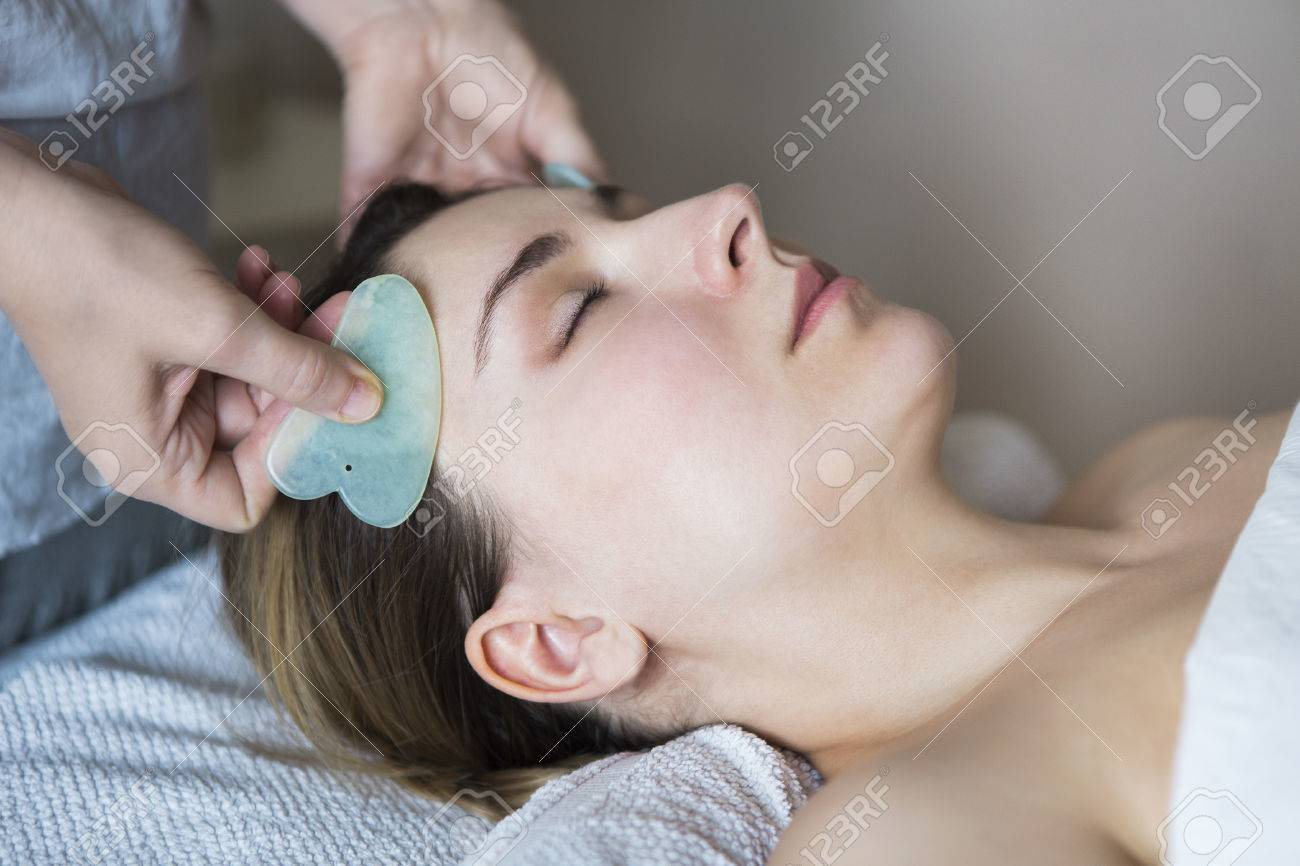 Young woman have face guasha treatment at asian beauty clinic - 84973875