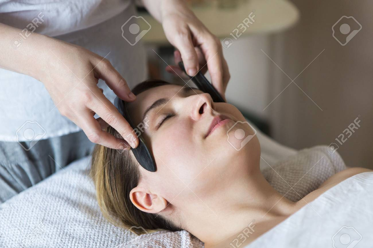 Young woman have face guasha treatment at asian beauty clinic - 85544222