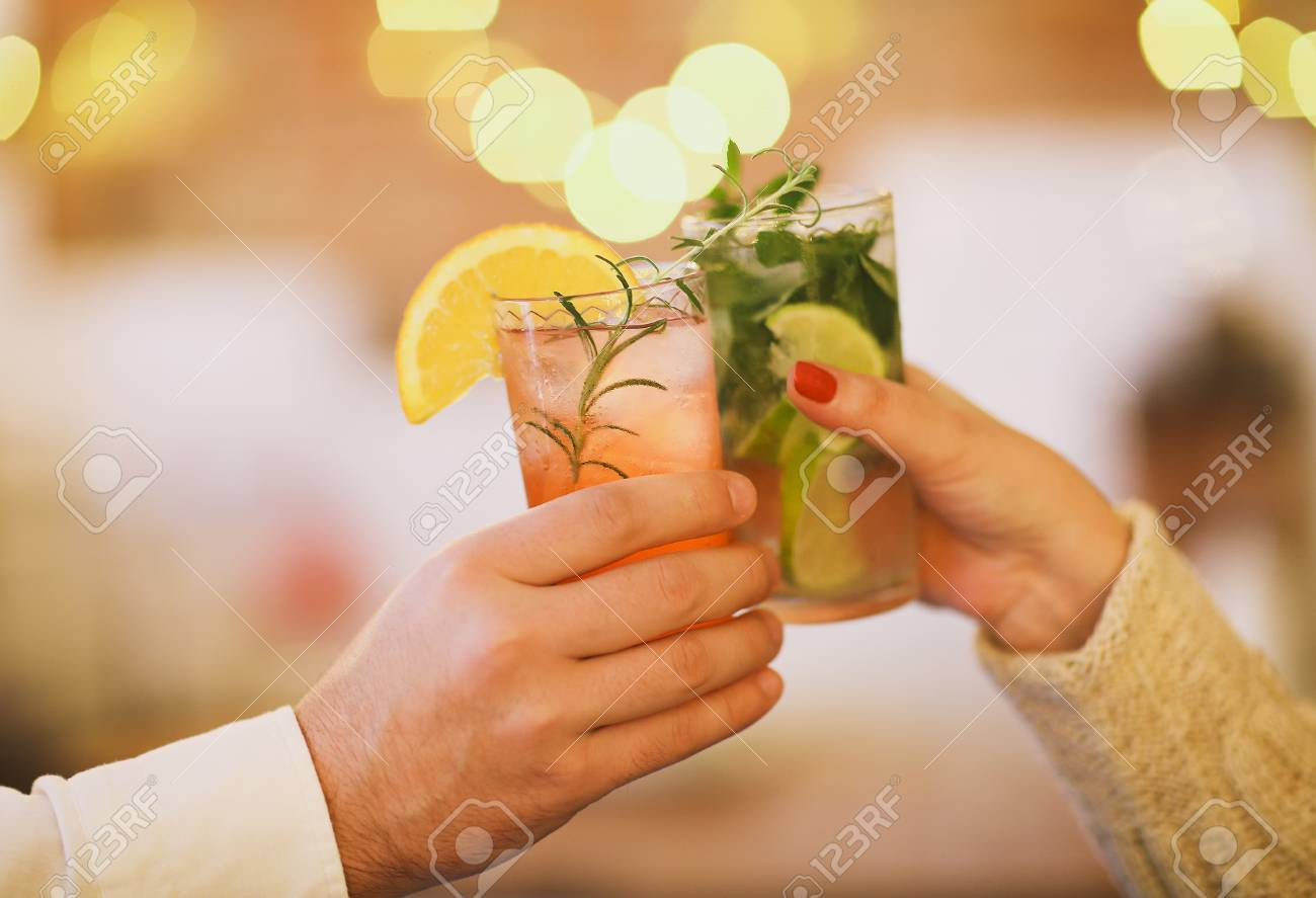 Two cocktail glasses in man and woman hand. Close up - 90707343