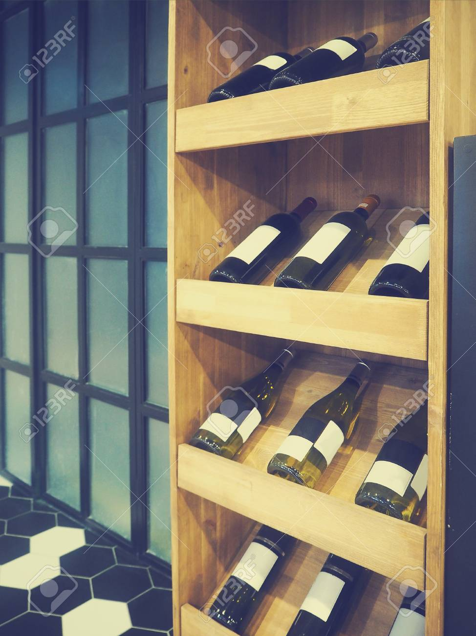 Bottles of red and white wine in rows in wine shop. Vintage toned Stock  Photo