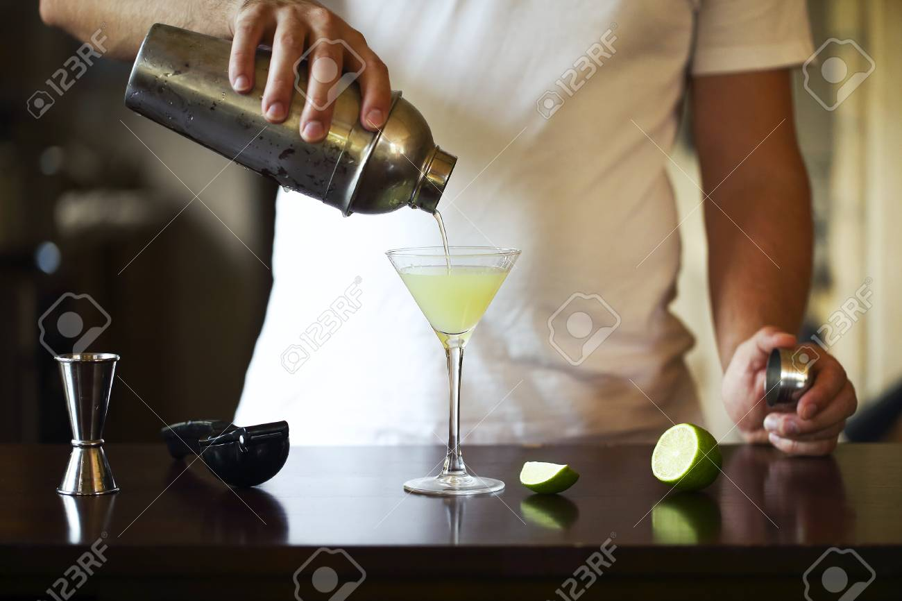 Barman at work, preparing cocktails. Pouring martini to cocktail glass. Service and beverages concept - 116815037