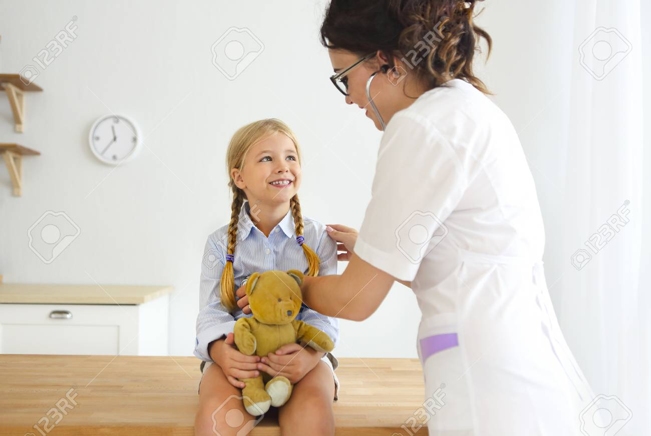 Young smiling female doctor and her little patient with teddy bear - 117784769