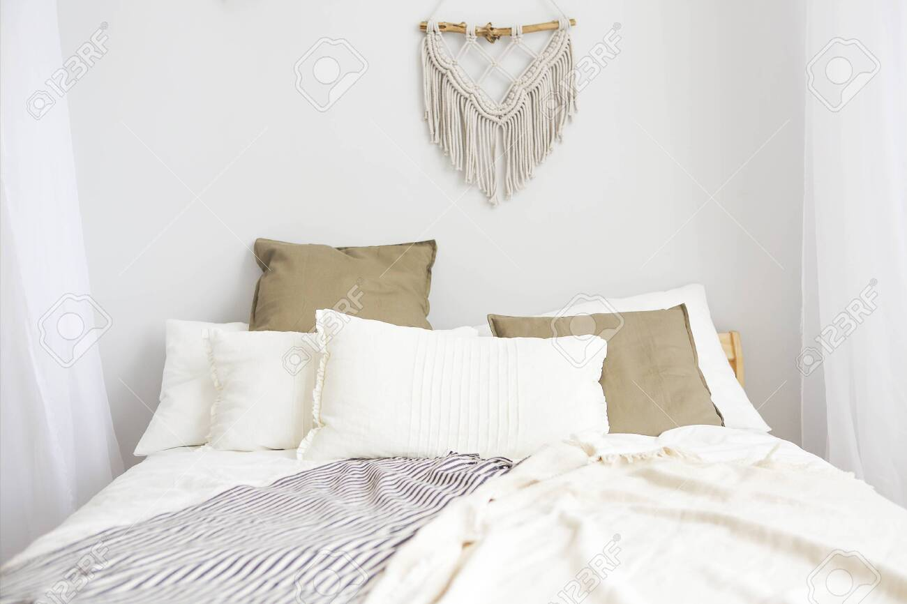 White and beige bedroom in boho style with macrame on the wall