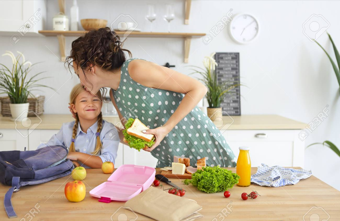 Beautiful brunette mother and her daughter packing healthy lunch and preparing school bag in the kitchen - 117788803