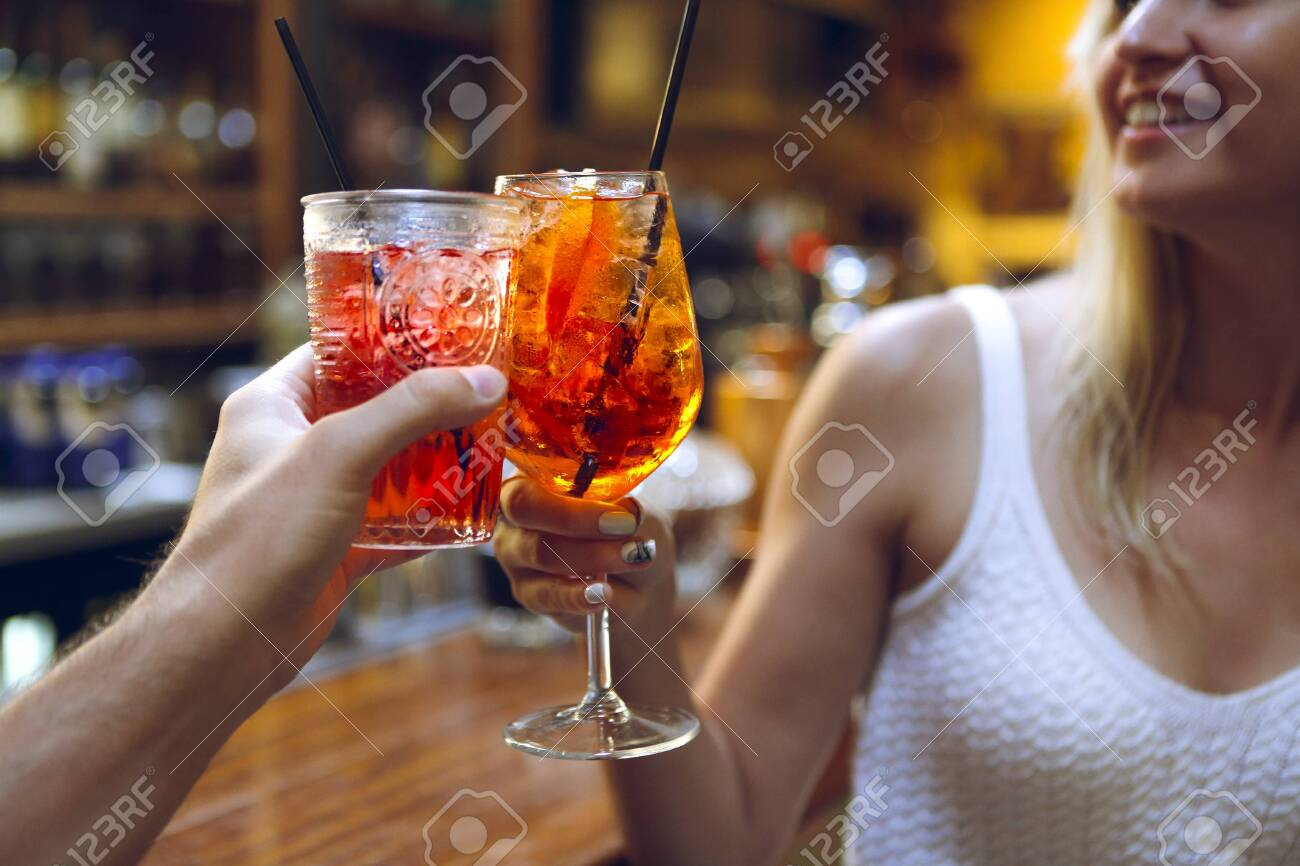Woman and man raising a glasses of coktails in the bar background - 133884964