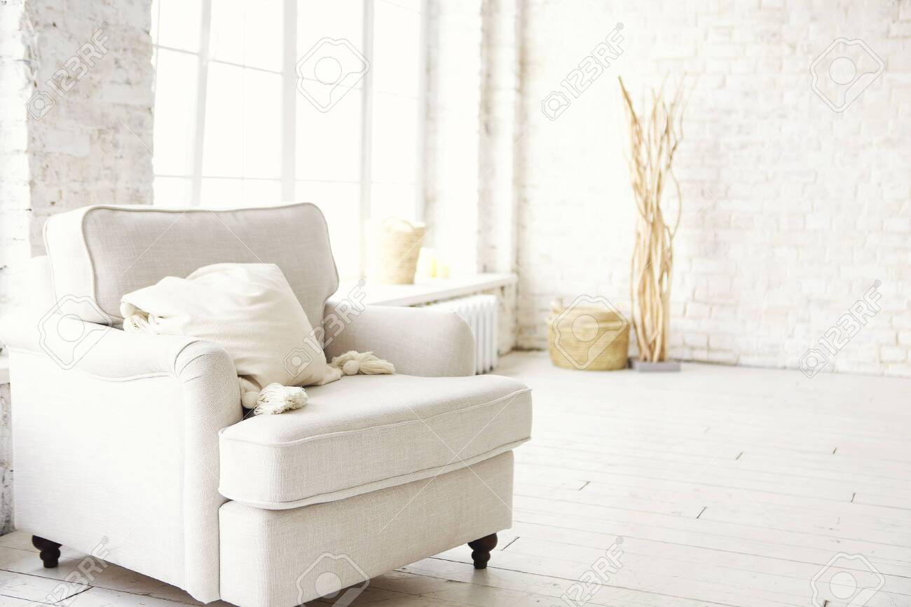 photo white armchair standing on the floor in front of a window shedding light on the interior of boho sty