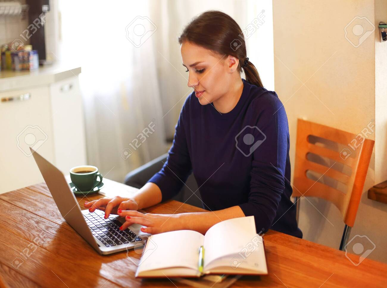 Youg female freelancer typing on laptop while working remotely from home at wooden table with books - 149361767