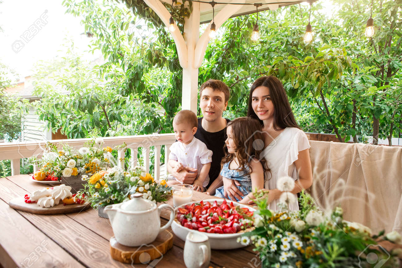 Loving family with kids sitting at table with delicious desserts and flowers during breakfast in countryside in summer - 168431908
