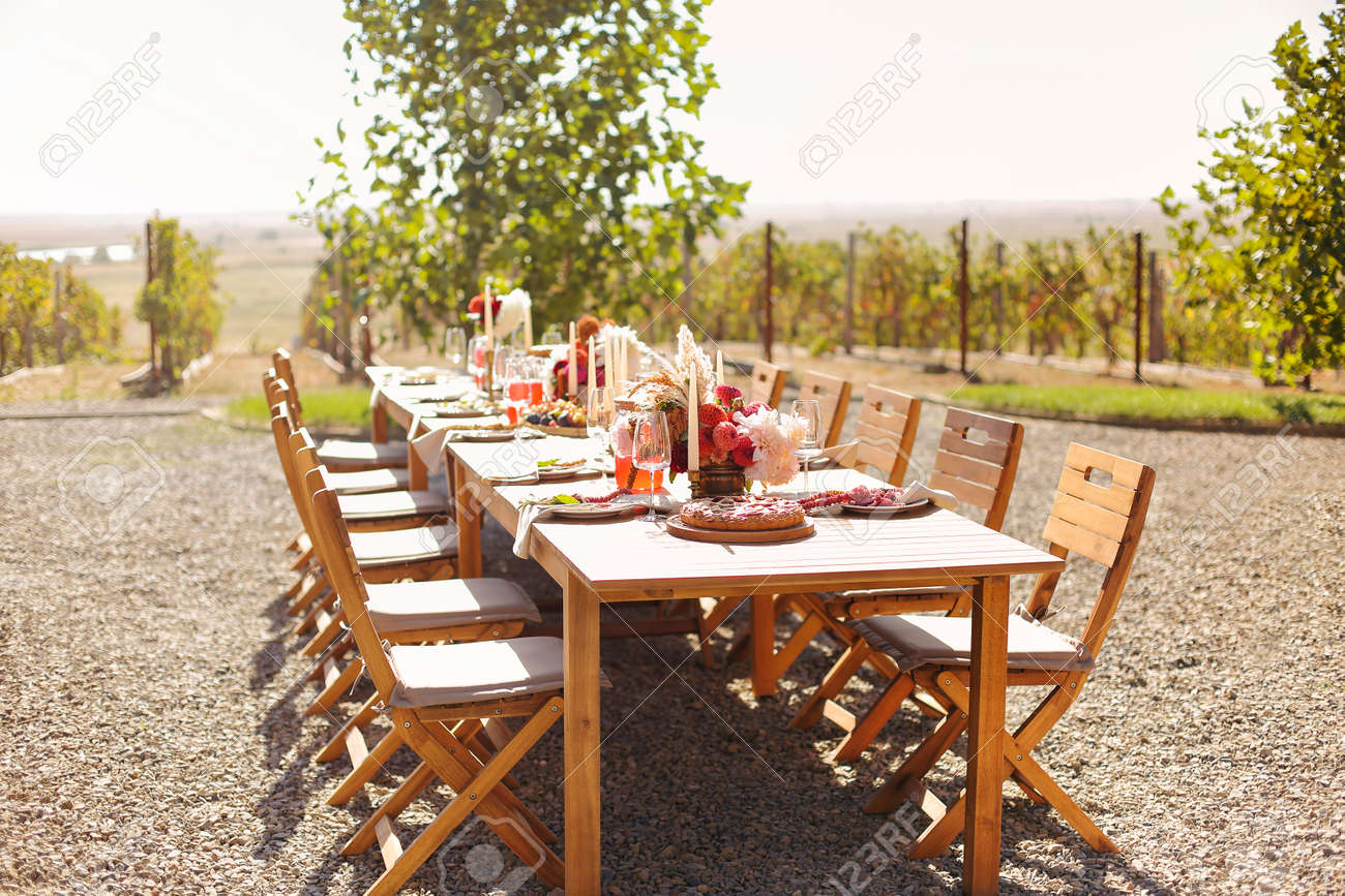 Empty wineglass placed near board with fruits on banquet table on sunny summer day - 169389624