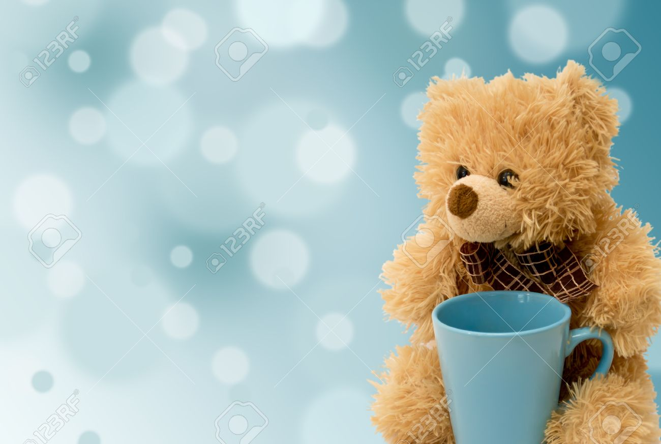 teddy bear with a blue cup on a blue background stock photo picture