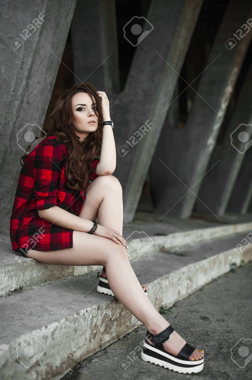 051f58c24321a9 Beautiful young hipster girl posing and smiling near urban wall background  in red plaid shirt,