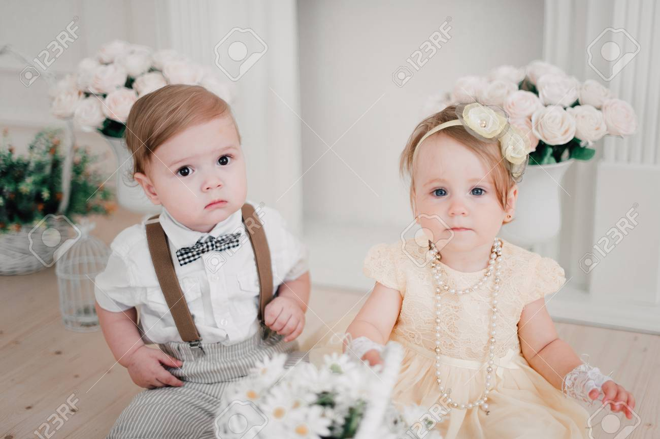 two babies - boy and girl dressed as bride and groom stock photo