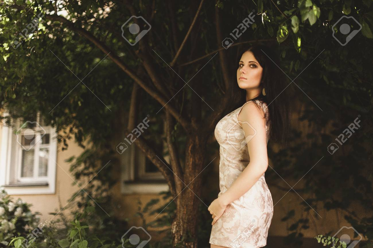 Beautiful young woman sexy brunette girl with make-up courtyard, dressed in  light dress