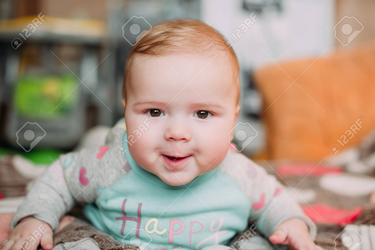 9782c25e3 little cute baby toddler on carpet close up smiling adorable happy  emotional playing at home Stock