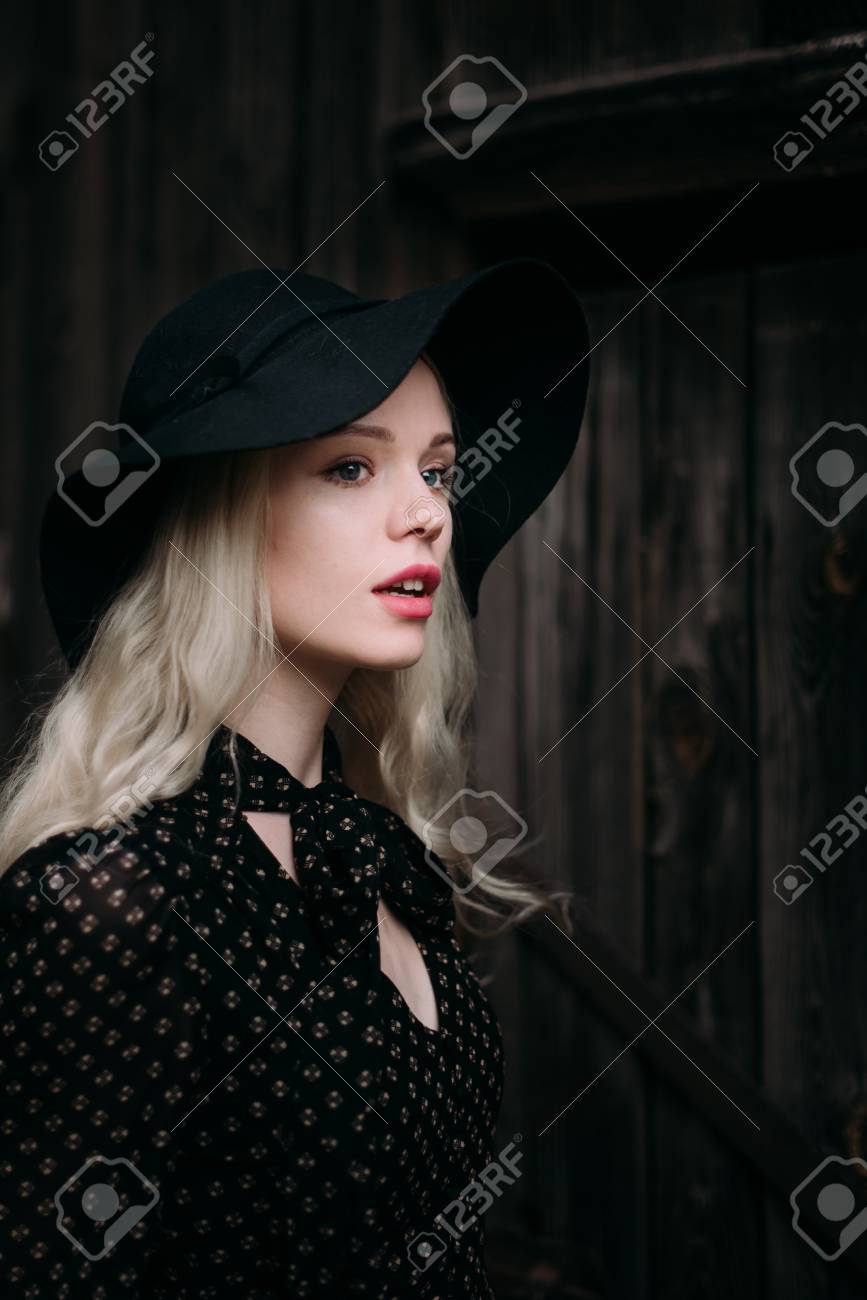 Beautiful attractive and stylish girl wearing black hat standing posing in  city. Nude makeup 7bc62ebfb7b