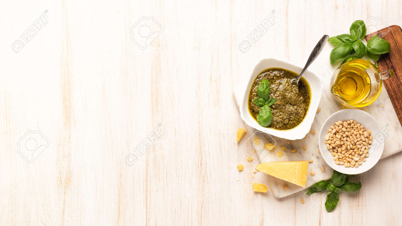 Bowl with pesto and fresh basil, garlic, parmesan cheese, pine nuts and olive oil on marble board. Kitchen wooden table with Italian sauce - 154742213